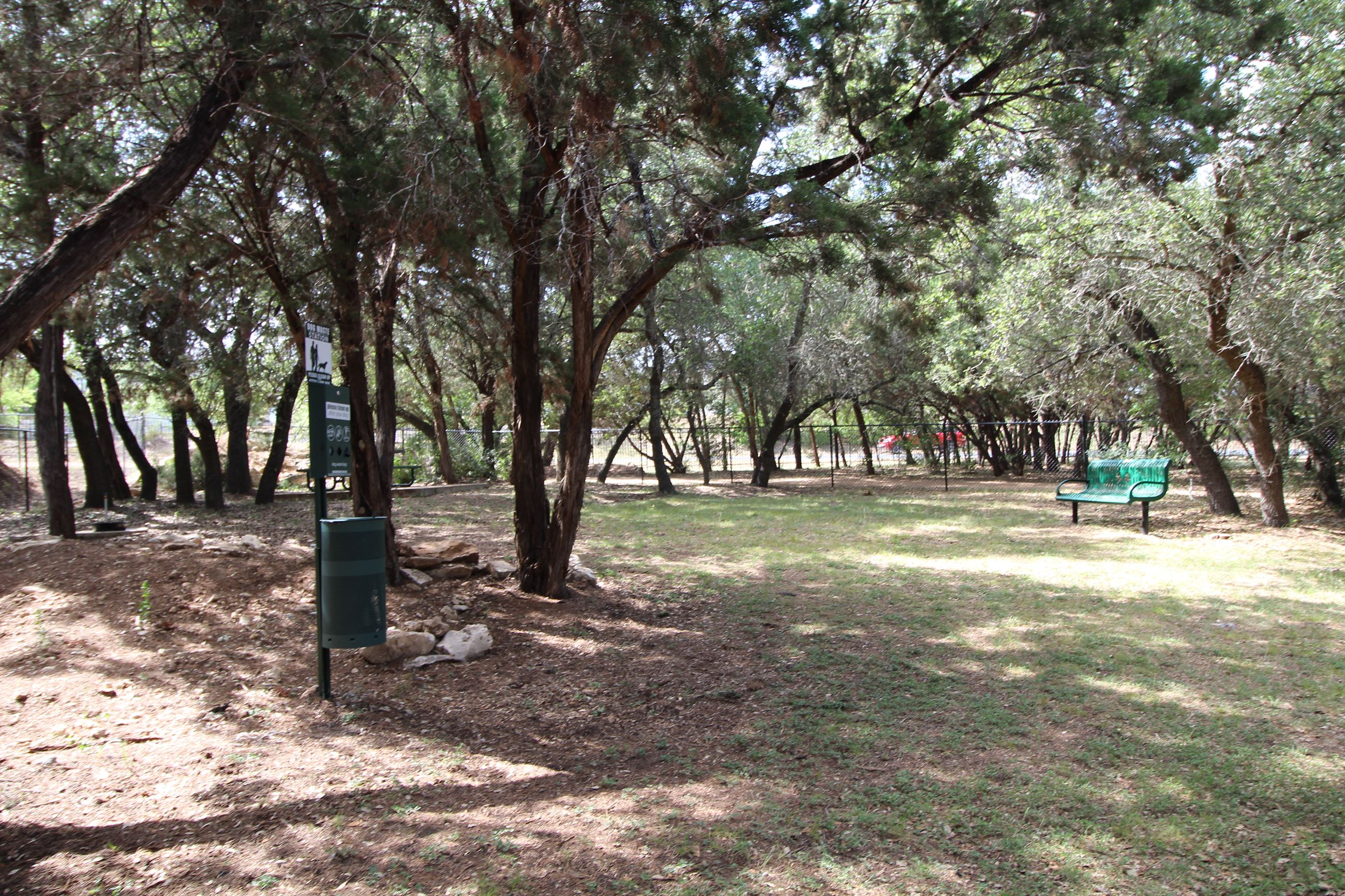 The small dog park, with plenty of room to explore and a bench for human companions.